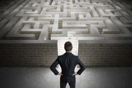 Businessman is searching exit path in maze. Strategy and decision concept. View from behind. Zdjęcie Seryjne