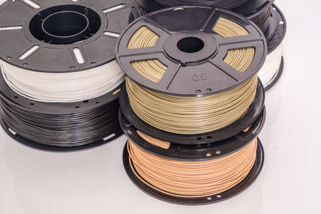 Many spools of plastic filament for 3D printer. Different colors.