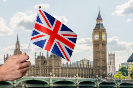 Toursist in London holding flag of Great Britain in hand. Big Ben in background.