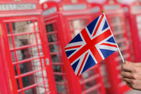 Flag of Great Britain and many London red phone booths in background. Stockfoto