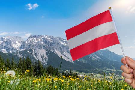 Hand of tourist is holding austria flsg. View from Rittisberg mountain on Dachstein in Alps. Reklamní fotografie
