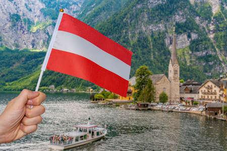 Tourist is holding austrian flag in Hallstatt in Austria. Travel concept.