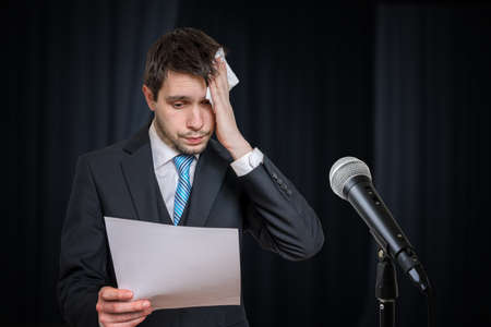 Sweating nervous speaker is afraid of public speech. Microphone in front.