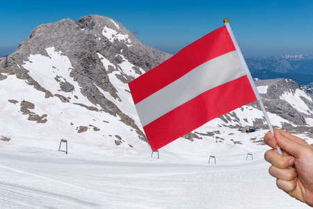 Hand of tourist is holding austria flag in hand. Alps in background.