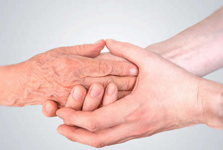 Man holds hands of eldery woman. Senior help and assistance concept.