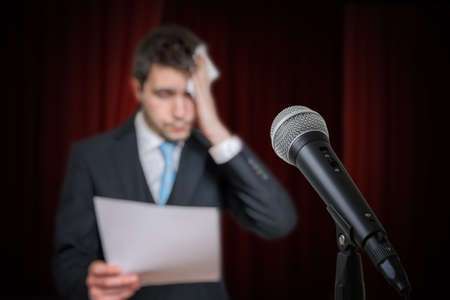 Nervous speaker is afraid of public speech and is sweating. Microphone in front.