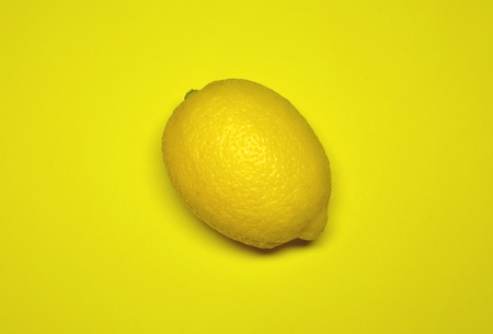 close up image: juicy lemon on a yellow background