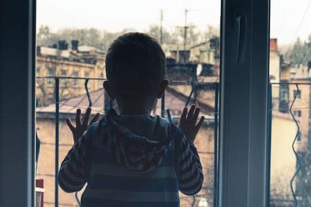 persona triste: Niño pequeño que mira a la ventana exterior Foto de archivo