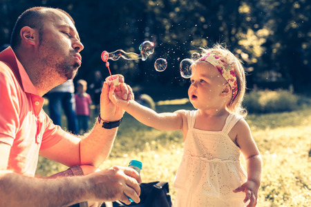 single family: daddy and daughter blowing a bubbles in the park