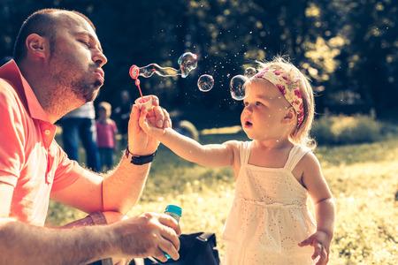 niñas jugando: Papá e hija soplando un burbujas en el parque