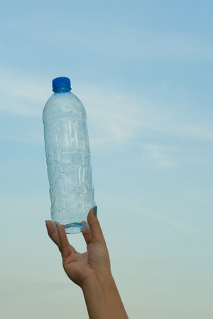 gulp: Woman hand holding a bottle of water in the sky background Stock Photo