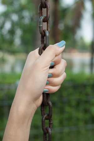 submissiveness: Woman holding chain on green background