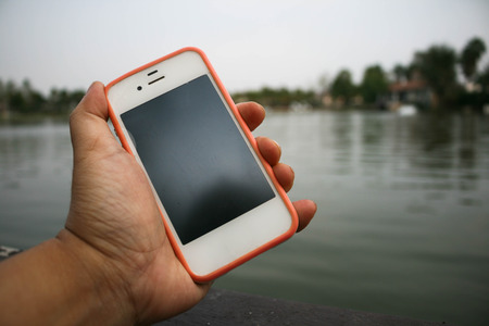 hand held: hand held mobile phone beside lake background Stock Photo