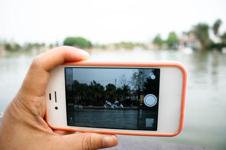hand held: tenuto in mano il telefono cellulare nei pressi del lago di sfondo