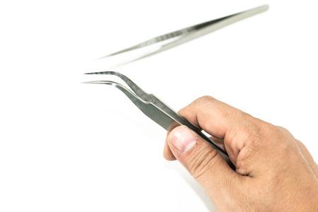 pinzas: mano que sostiene pinzas de metal aislar en el fondo blanco