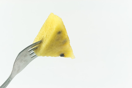 stab: Fork stab on yellow watermelon isolate on white background