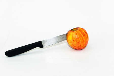 stab: Knife stab on red apple on white background Stock Photo