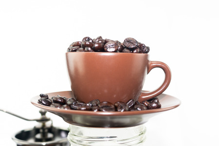 Coffee beans overflow in coffee ceramic cup and dish Stock Photo
