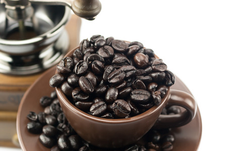 a jar stand: Coffee beans overflow in coffee ceramic cup and dish Stock Photo