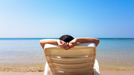 Woman lay on white plastic armchair on the wet beach in hot sunny time with shadow beside the blue sea