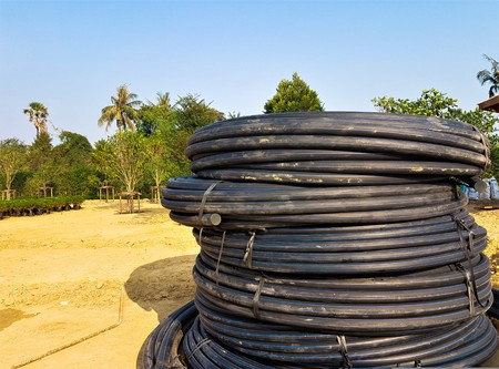 Black coil rubber hose put on the sand in the garden Stock Photo