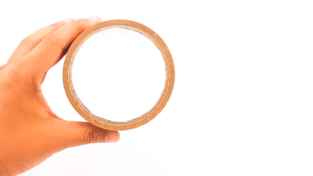 Man hand holding thick brown plastic tape with big core isolated