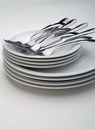 Silverware on a stack on white plates on a white background, vertical