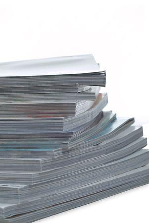 Shallow focus strack of magazine on white backround Banco de Imagens