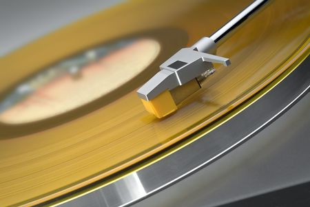 Tilted close up of headshell and stylus on a turntable with yellow vinyl record 版權商用圖片
