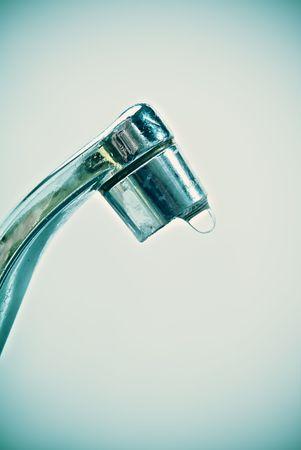 Geneigte Ansicht eines alten tropfenden Wasserhahn in einem Cross-Prozess Farbe  Lizenzfreie Bilder