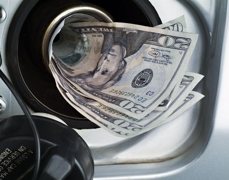 A close up of an automotive gas filler being filled with money