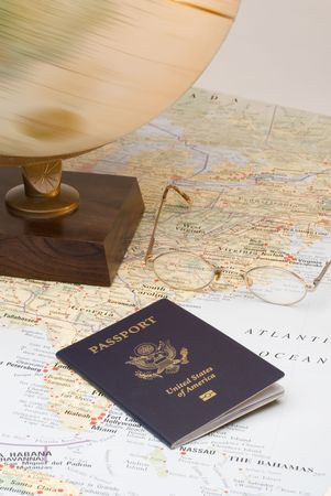 A US Passport and a spinning globe on a map. Planning a trip or vacation to somewhere. Stock Photo