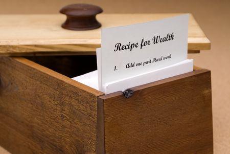 Een concept van een recept voor rijkdom op een recept kaart in een houten doos recept