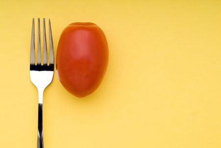 snappy image of a fork and a tomato on a bright yellow background
