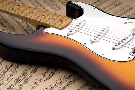 Electric guitar with a worn maple neck laying on sheet music printed on parchment paper