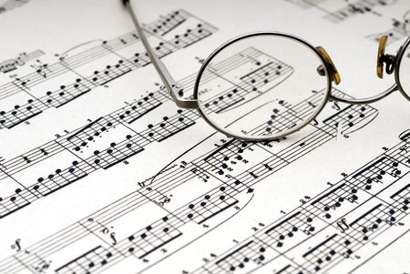 Old reading glasses resting on old sheet music