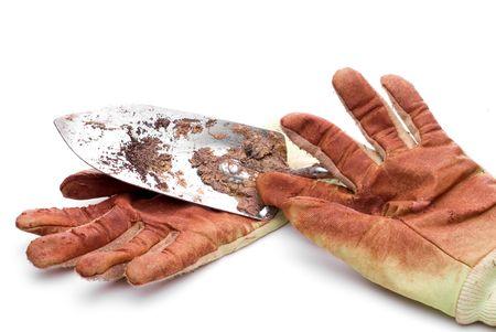 Dirty worn gardening gloves with a garden spade