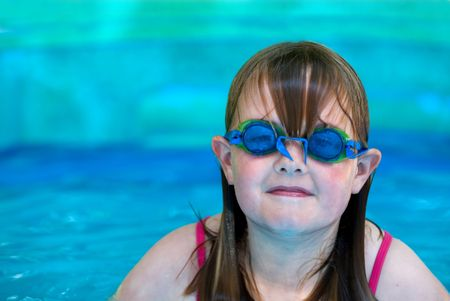 space for type: A young girl with swimming goggles in an inflatable pool with space on left for type Stock Photo