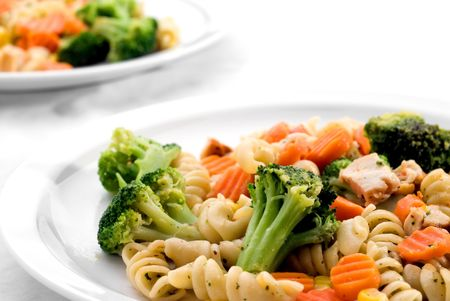 Two dishes of pasta with mixed vegatables