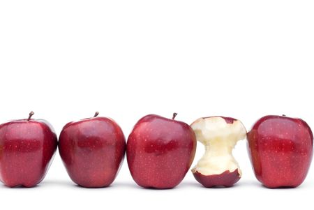 Red apples line up on a white background with on eeaten apple