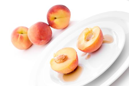 shallow focus fresh peaches drizzled with maple syrup on a white plate
