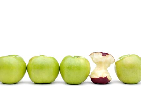 Green apples lined up on a white background with a single eaten red apple