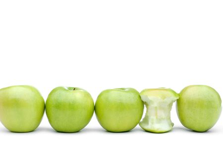 green apples line up on a white background with one eaten apple