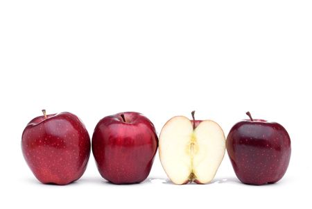 Red apples line up on a white background with one sliced apple