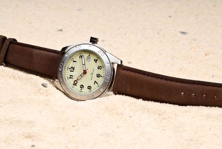 A watch in sand representing The Sands of Time