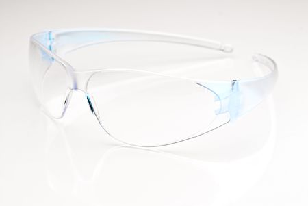 Modern safetly glasses on a reflective surface