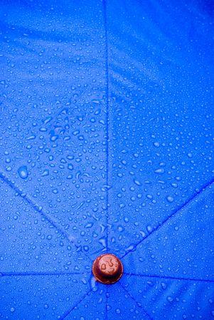 drizzling rain: A closeup of a wet blue unmbrella Stock Photo