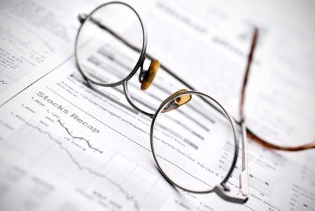 Glasses on a newspaper stock report Imagens