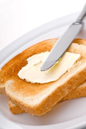 Un cuchillo en la mantequilla la difusi�n de pan tostado en un plato blanco