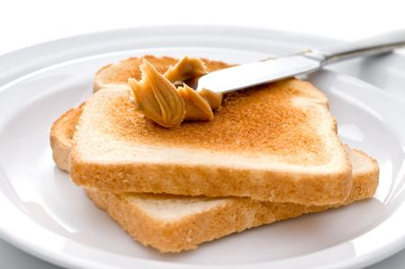 Spreading peanut butter on toast